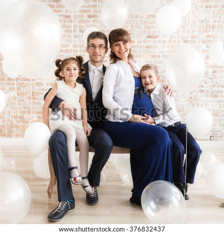 Happy family with mom dad and two baby under lots of white helium balloons.  - stock photo