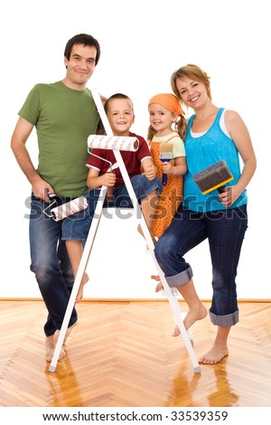 Happy family with painting utensils ready to repaint their home - isolated - stock photo