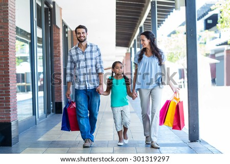 Happy family with shopping bags at the mall - stock photo