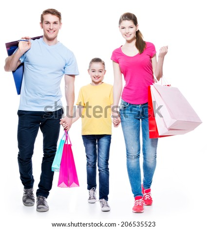 Happy family with shopping bags standing at studio over white background. - stock photo