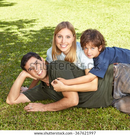 Happy family with son laying in summer in grass of a garden - stock photo