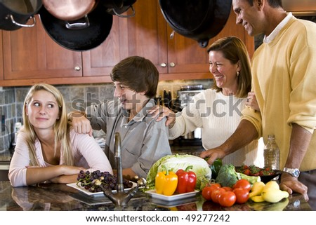Happy family with teenagers smiling in kitchen - stock photo