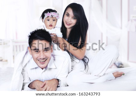 Happy family with the baby playing on the bed at home - stock photo