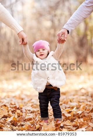 happy family with their baby spending time outdoor in the autumn park  and teaching her walking - stock photo