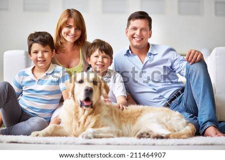 Happy family with two boys and a dog smiling at camera - stock photo