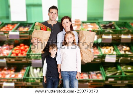Happy Family With Two Children Holding Groceries Bag Full Of Vegetables - stock photo