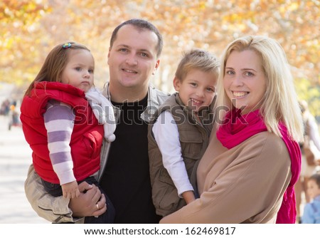 Happy family with two children in autumn park - stock photo
