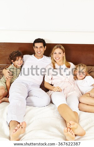 Happy family with two children laying on bed in bedroom - stock photo