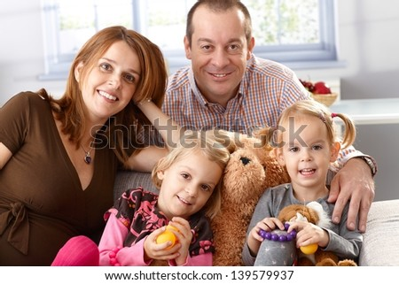 Happy family with two daughters and pregnant mother at home. - stock photo