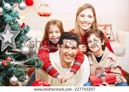 Happy family with two kids at christmas with gifts - stock photo