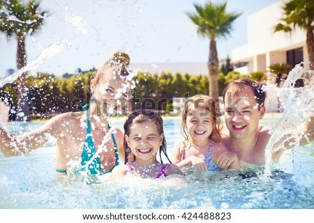 Happy family with two kids having fun in the swimming pool. Summer vacation concept - stock photo