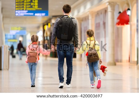 Happy family with two kids in airport have fun waiting for boarding - stock photo