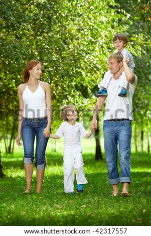 Happy family with two small sons goes on a summer garden - stock photo