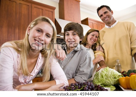 Happy family with two teenagers standing together in kitchen - stock photo