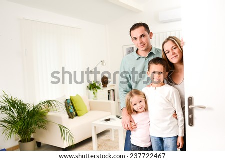 happy family with young kids welcoming a guests at their house door wide open. - stock photo
