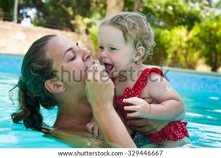 Happy family, young active mother and adorable curly little baby having fun in a swimming pool, child learning to swim in an inflatable toy ring, enjoying summer vacation at a tropical resort - stock photo