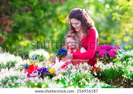 Happy family, young beautiful mother and her daughter, cute little toddler girl, playing together in the garden planting and watering flowers on a sunny summer day. Kids gardening. Family outdoors. - stock photo