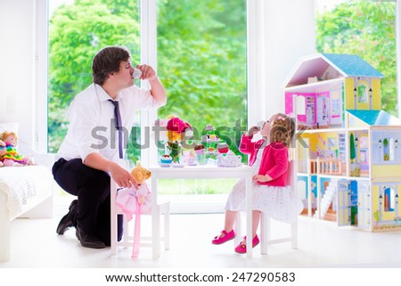Happy family, young father and his little daughter, cute curly toddler girl wearing a dress, playing together with doll house, having toy tea party in a white sunny nursery - stock photo