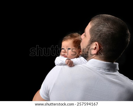 Happy family young father and new born infant child baby girl kissing and hugging on black background - stock photo