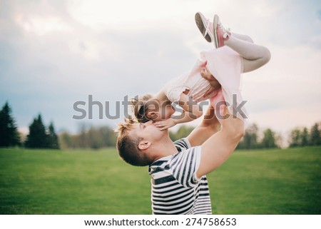 Happy family. Young father playing silly with his daughter lifting her up - stock photo