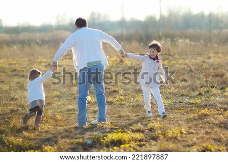 Happy family: young father with his little children walking in the field in summer morning. Strong healthy daddy spinning with his daughter and his son.  - stock photo