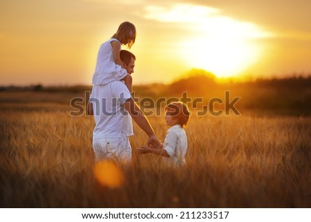 Happy family: young father with his little children walking in the wheat field at sunset in a warm summer evening. Daughter sitting on her father's shoulders and son holding his father by hand  - stock photo
