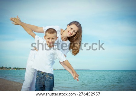 Happy family. Young happy beautiful  mother and her son having fun on the beach. Positive human emotions, feelings, emotions. - stock photo