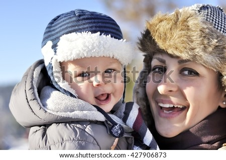 Happy family. Young mother in a winter park with her sweet baby boy - stock photo