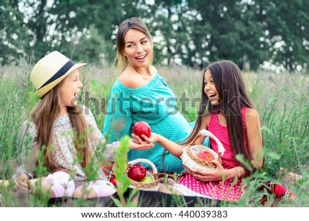 happy family young pregnant woman and children daughters on picnic - stock photo
