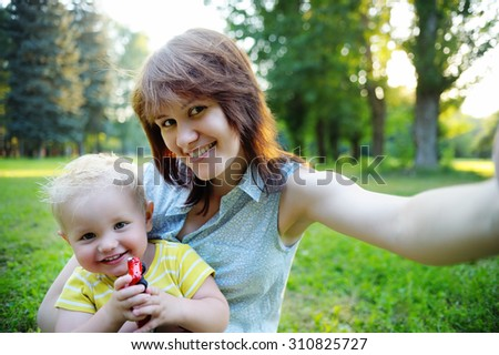 Happy family: young woman and her adorable toddler son at park making selfie - stock photo