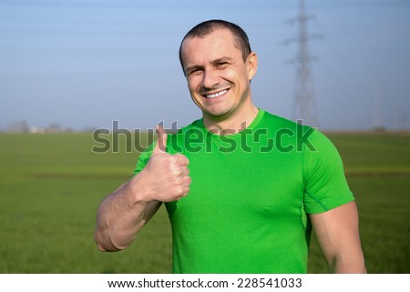 happy farmer (businessman) standing in wheat field over wind turbines background and showing ok (thumbs up) - stock photo