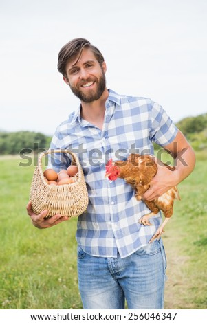 Happy farmer holding chicken and eggs on a sunny day - stock photo