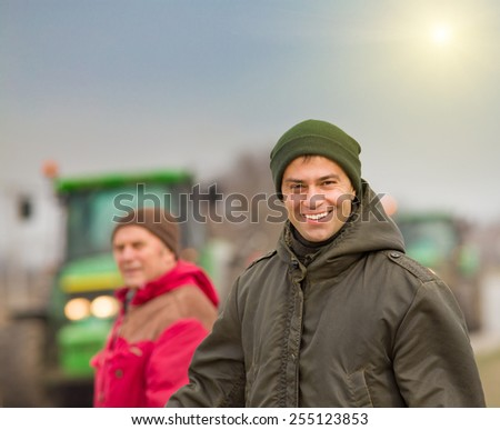 Happy farmer standing on farmland with tractors in background - stock photo