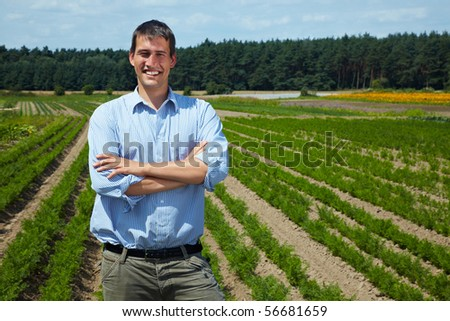 Happy farmer with arms crossed in front of his fields - stock photo