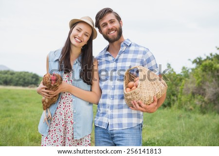 Happy farmers holding chicken and eggs on a sunny day - stock photo