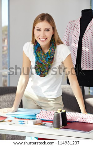 Happy fashion designer standing in her office with dress form - stock photo