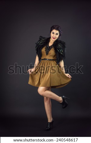 Happy fashion woman dressed in a gold dress and feathers collar. New Year's Eve Party. Statement Necklace - stock photo