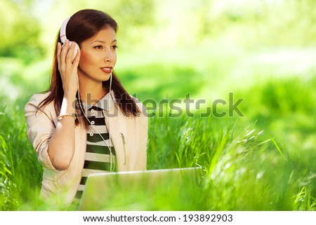 Happy fashionable hipster girl in pink leather jacket listening to the music on computer, sitting in green grass in the park. Sunny day. Copy-space. Outdoor shot - stock photo