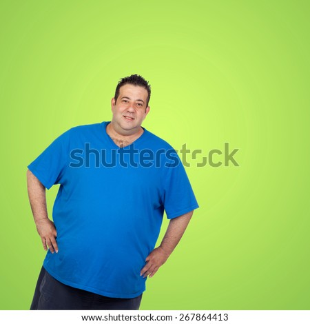 Happy fat man with blue shirt and a green background - stock photo