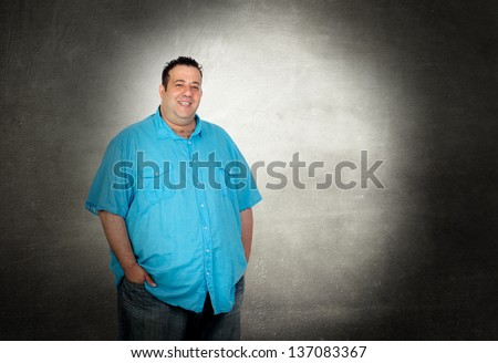 Happy fat man with blue shirt on a over gray background - stock photo