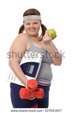 Happy fat woman eating green apple, holding dumbbells and scale in sportswear. - stock photo
