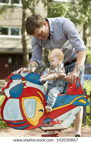 Happy father and baby son have fun at playground - stock photo