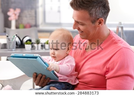 Happy father and beautiful baby daughter using tablet computer. - stock photo