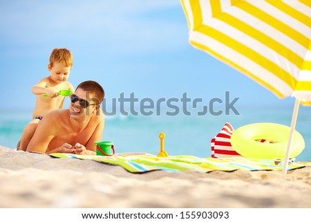 happy father and child having fun in sand on the beach - stock photo