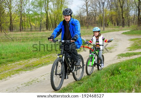 Happy father and child on bikes, family cycling ourdoors  - stock photo