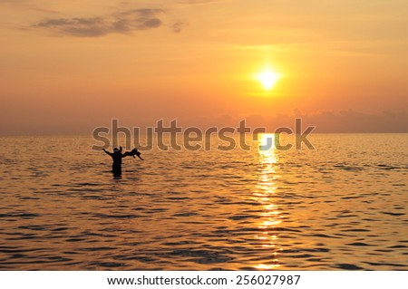Happy father and child swimming in the sea at beautiful colorful sunset - stock photo