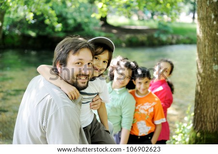 Happy father and  children together outdoor, faces, smiling and careless - stock photo