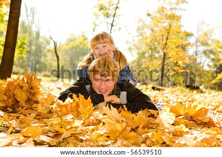 Happy father and daughter in autumn park lying on yellow leaves - stock photo