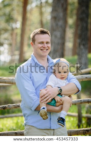 Happy father and daughter sitting on dad's hands playing in the park - stock photo