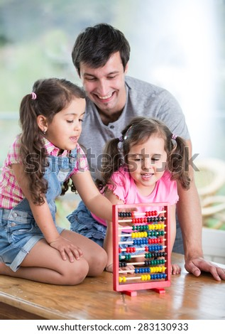 Happy father and daughters playing with abacus in house - stock photo
